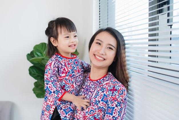 아오자이 전통 의상을 입은 베트남 어머니와 딸이 집에서 새해를 축하합니다. 테트 홀리데이.