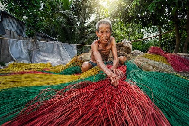 Вьетнамский старик-мастер делает традиционные вьетнамские циновки в старой традиционной деревне