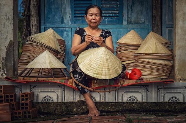 오래된 전통 가옥에서 베트남 전통 모자를 만드는 베트남 노파 장인