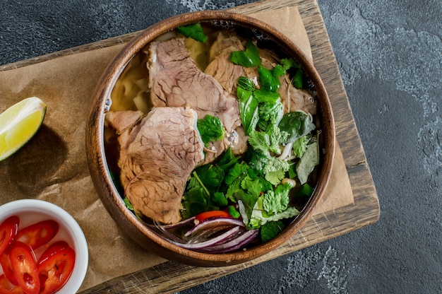 Vietnamese pho bo soup in a wooden bowl on dark background
