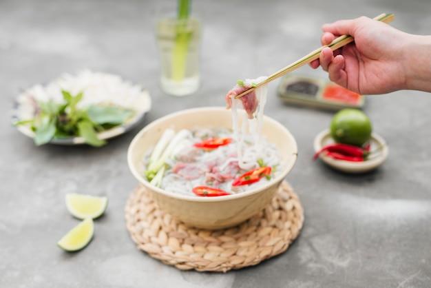 ベトナムのフォーヌードルスープ。唐辛子入り牛肉、バジル、ライスヌードル、箸でとった麺を示す豆もやし