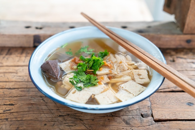 나무 테이블에 돼지 고기와 닭고기와 베트남 쌀 국수 수프