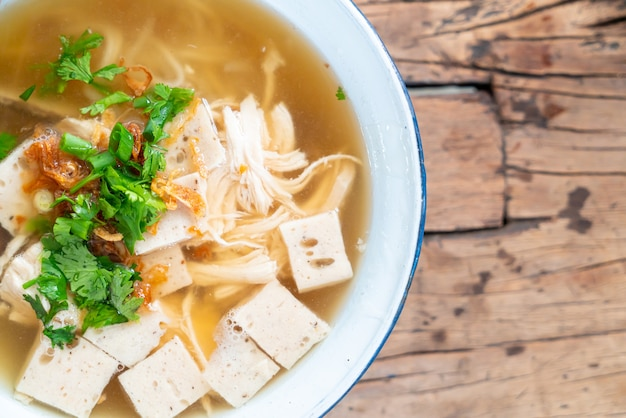 Vietnamese rice noodle soup with pork and chicken on wood table