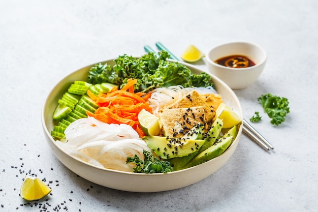 Vietnamese rice noodle with grilled tofu and  chilli vegetables salad in white bowl, copy space.