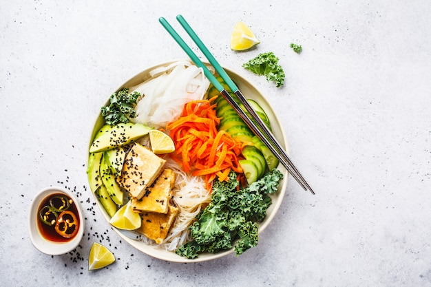 Vietnamese rice noodle with grilled tofu and  chilli vegetables salad in white bowl, top view.