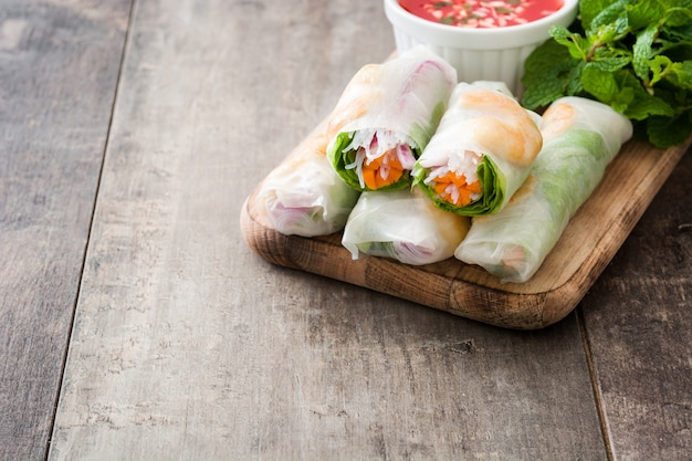 Vietnamese rolls with vegetables, rice noodles and prawns on wooden copy space