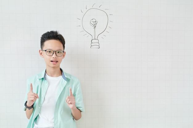 Вьетнамский школьник стоит у доски с рисунком лампочки и указывает вверх указательными пальцами
