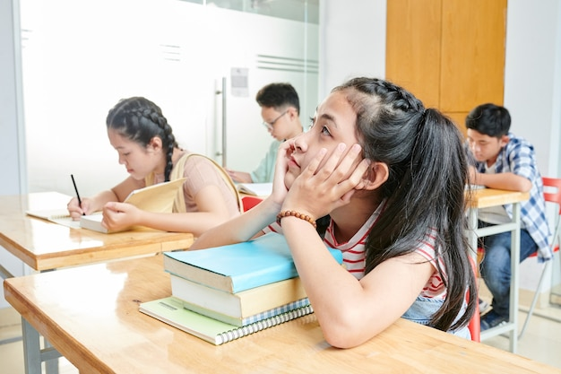 Vietnamese schoolgirl sitting at her desk with stack of books and dreaming instead of studying at english lesson