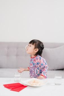 アオザイの伝統的なドレスを着たベトナムの小さな女の子は、家で新年を祝います。テトホリデー。