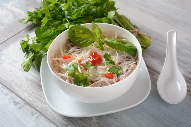 Vietnamese soup pho bo with herbs, beef, rice noodles, chili, and  bean sprouts