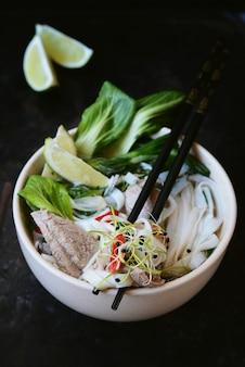 ベトナムのスープフォーボーとボウルに野菜とライスヌードル