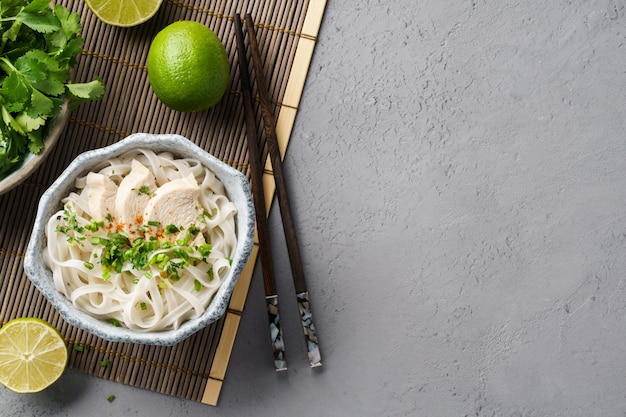 Vietnamese soup pho ga with chicken, rice noodles and herbs.
