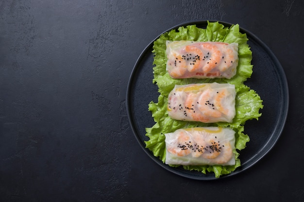 Vietnamese spring rolls with vegetables, prawns in rice paper on black. asian cuisine.