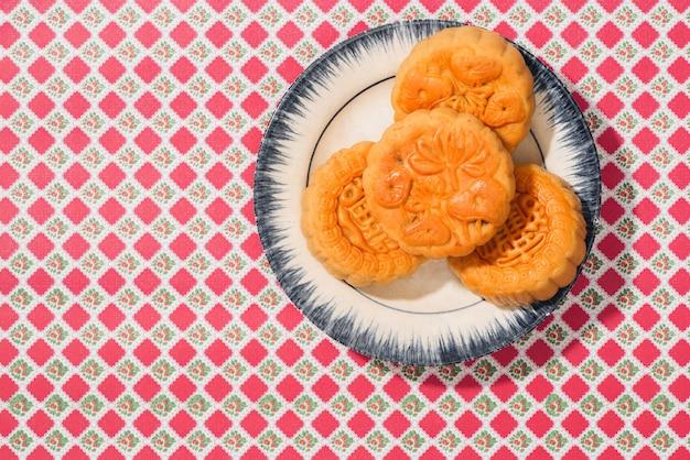 満月、黒い木製の背景の上から見た月餅の中秋節のためのベトナムの甘い食べ物。丸月餅「中秋節」の翻訳。