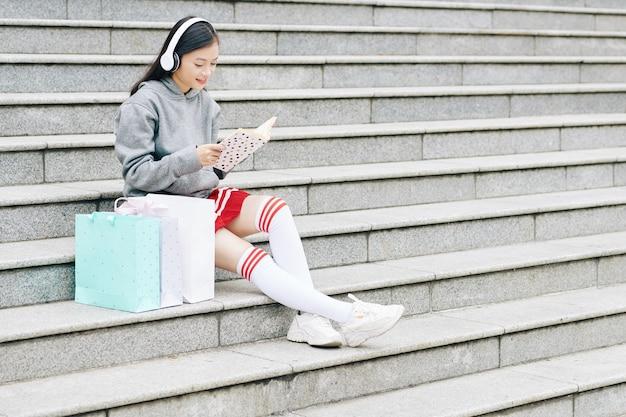 Вьетнамская девочка-подросток сидит на ступеньках рядом с сумками, слушает музыку в наушниках и читает интересную книгу
