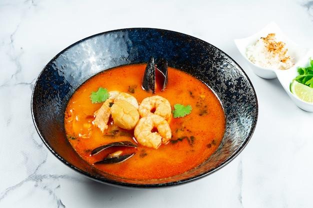 Вьетнамский суп tom yum с морепродуктами. красный суп с креветками, морским гребешком, мидиями, лососем в темной стильной миске на мраморном столе.