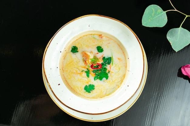 Вьетнамский суп tom yum с морепродуктами. желтый суп с креветками, морским гребешком, мидиями, лососем в темной стильной миске на мраморном столе.