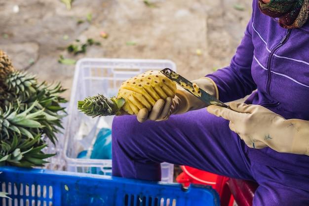 Вьетнамская женщина чистит ананас