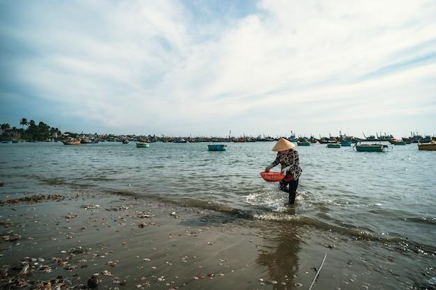 円錐形の帽子をかぶったベトナム人女性が海のバスケットで貝を洗います。ムイネー。ベトナム。 2019年1月27日