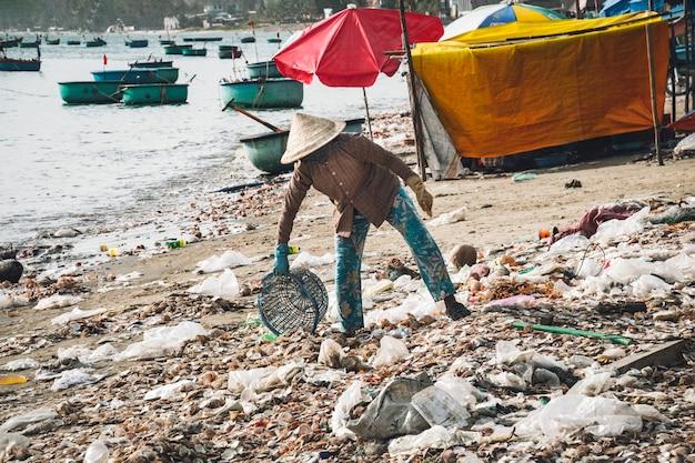 ベトナム人女性が海沿いのビーチにゴミを捨てる。海沿いに捨てる。東南アジアの悪い生態。ベトナム、ムイネーの漁師村