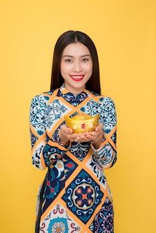 Традиционный праздничный костюм вьетнамской женщины ао дай. тет-праздник. лунный новый год. текст означает богатый.