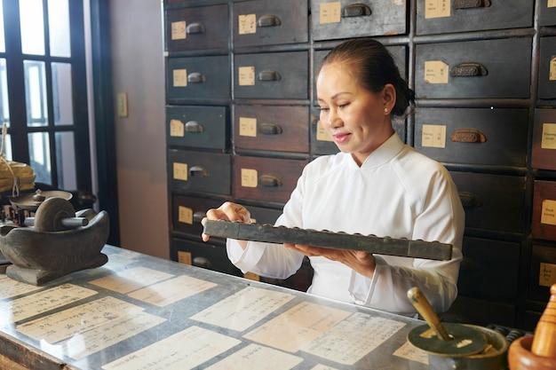 伝統的な薬剤師で働くベトナム人女性