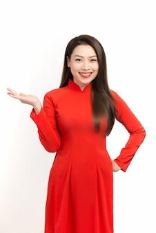 ベトナムの女性が伝統的なアオザイを着て、白を着て紹介する