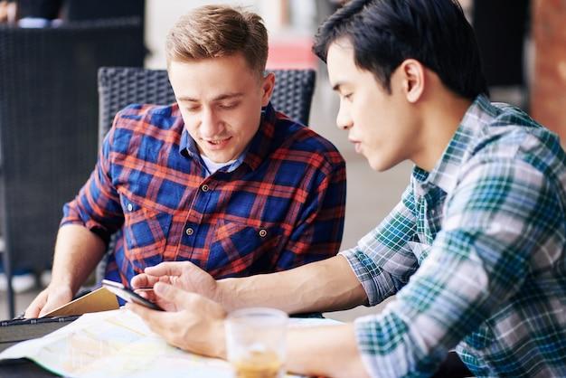 彼らがカフェテーブルに座っているときに友人に彼のスマートフォンで新しいモバイルアプリケーションを示すベトナムの若い男