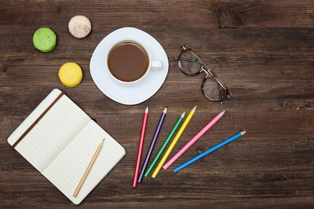 コーヒーマグ、色鉛筆、ノートブックのトップviev。木製の背景