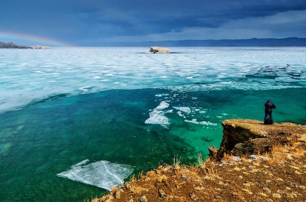Вид сверху на большое красивое озеро байкал с льдинами, плавающими на воде, и мужская спина фотографирует, россия