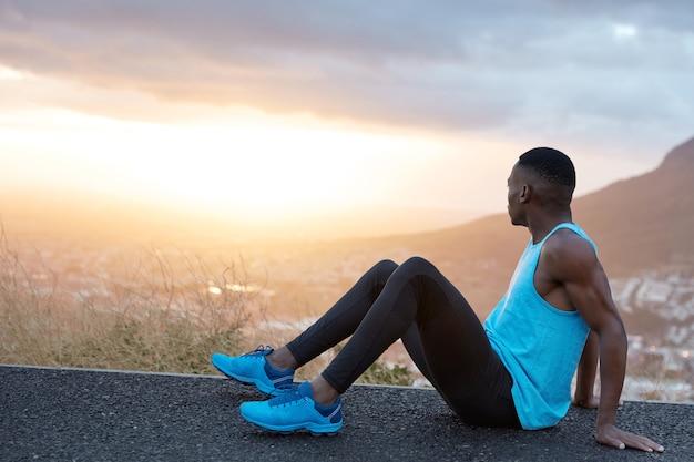 La vista del maschio attivo riposa dopo lo sprint, si siede sull'asfalto e si appoggia sulle mani, vestito con abbigliamento sportivo, scarpe da ginnastica blu, tiene lo sguardo da parte sull'immagine panoramica della natura di montagna, essendo pieno di energia