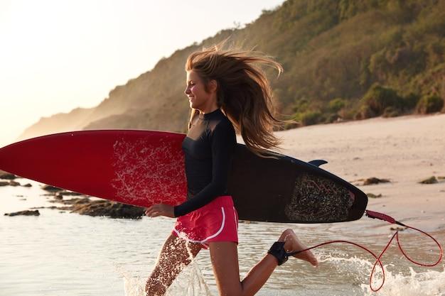 Vista della donna sportiva attiva corre sull'acqua nell'oceano caldo