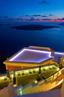 View of  the aegean sea at twilight with swimming pool in the foreground, santorini island, greece. greek landscape - cityscape