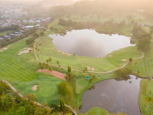 Вид с воздуха на лужайку поле для гольфа в утреннем или вечернем свете, красивый зеленый, приятный для глаз
