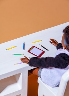 View on a african boy doll with pencils and paper on a table.