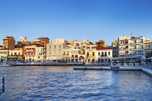 View of agios nikolaos at sunset. evening outdoor cafes on waterfront. greece, crete island