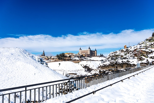 View of the alcazar and the city of toledo after the filomena snow storm. urban snowy landscape of the city.