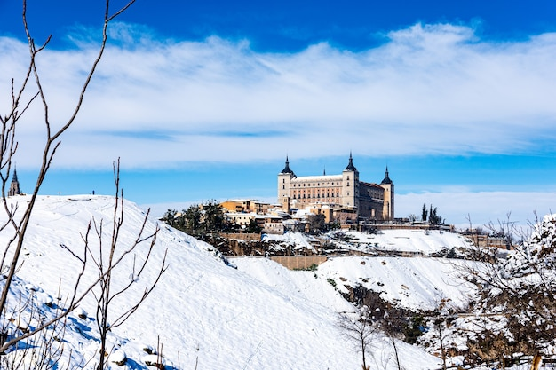 View of the alcazar of toledo after the filomena snow storm. urban snowy landscape of the city.