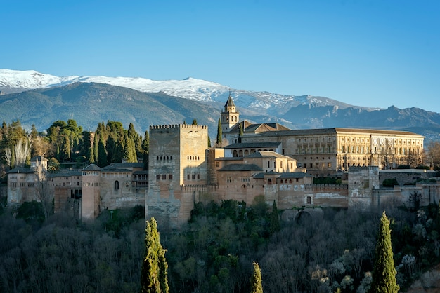 View of the alhambra and charles v palace with the sierra nevada national park in the background, in the city of granada, andalucia, spain
