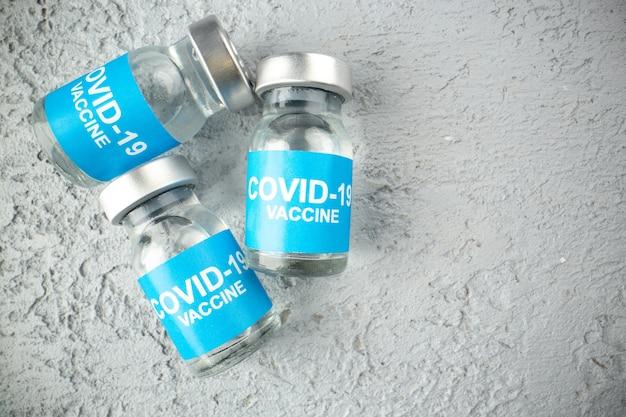 Vista dall'alto delle fiale con vaccino contro il covid su sfondo grigio sabbia con spazio libero