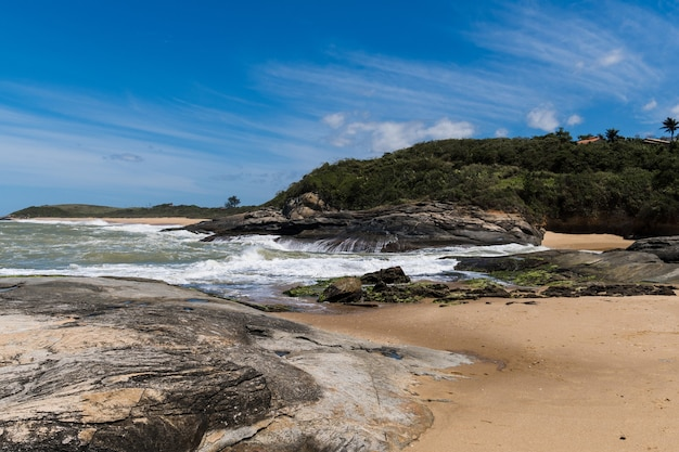 View of areia negras beach in rio das ostras in rio de janeiro with sunny day, blue sky and some clouds. strong sea and black sand mixed with yellow and many rocks.