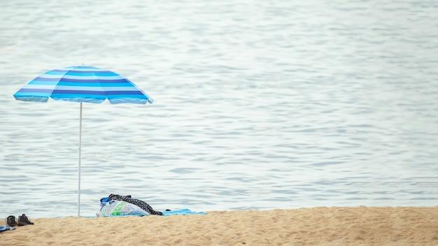 水辺の海岸線のビーチパラソルで見る