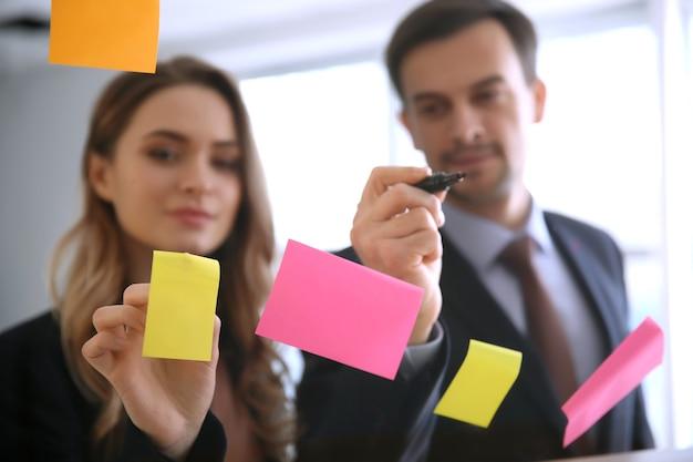 Вид на бизнес-команду во время встречи в офисе через прозрачную доску