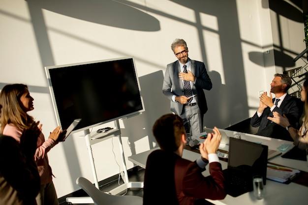 Посмотреть на группу деловых людей, работающих вместе и готовящих новый проект на встрече в офисе