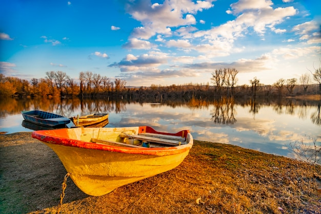 湖のほとりの地面にある古い黄色いボートを見る