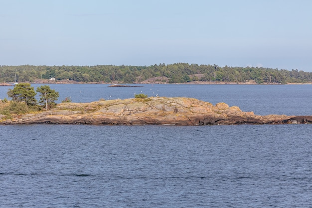 스웨덴의 해안선에서 무거운 구름과 큰 바위가 바다에서 나오는 발트 해를 봅니다. 프리미엄 사진