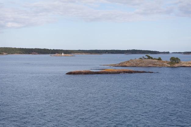 스웨덴의 해안선에서 무거운 구름과 큰 바위가 바다에서 나오는 발트 해를 봅니다.