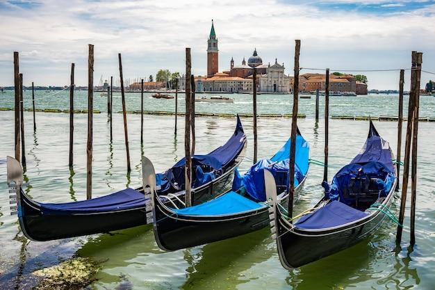 イタリア、サンジョルジョマッジョーレ島の前、ヴェネツィアの運河に浮かぶ伝統的なゴンドラを見る