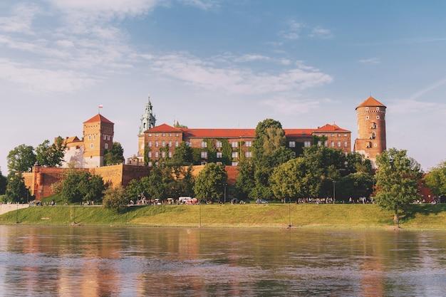 ポーランド、クラクフ市(クラクフ)のヴァヴェル城の眺めは、晴れた夏の日にヴィスワ川に反映されます。