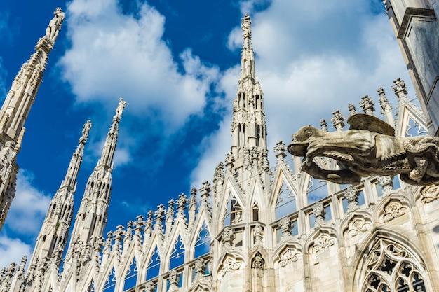 イタリアの有名なミラノのドゥオーモ大聖堂の屋根にある白い大理石の彫像を見る